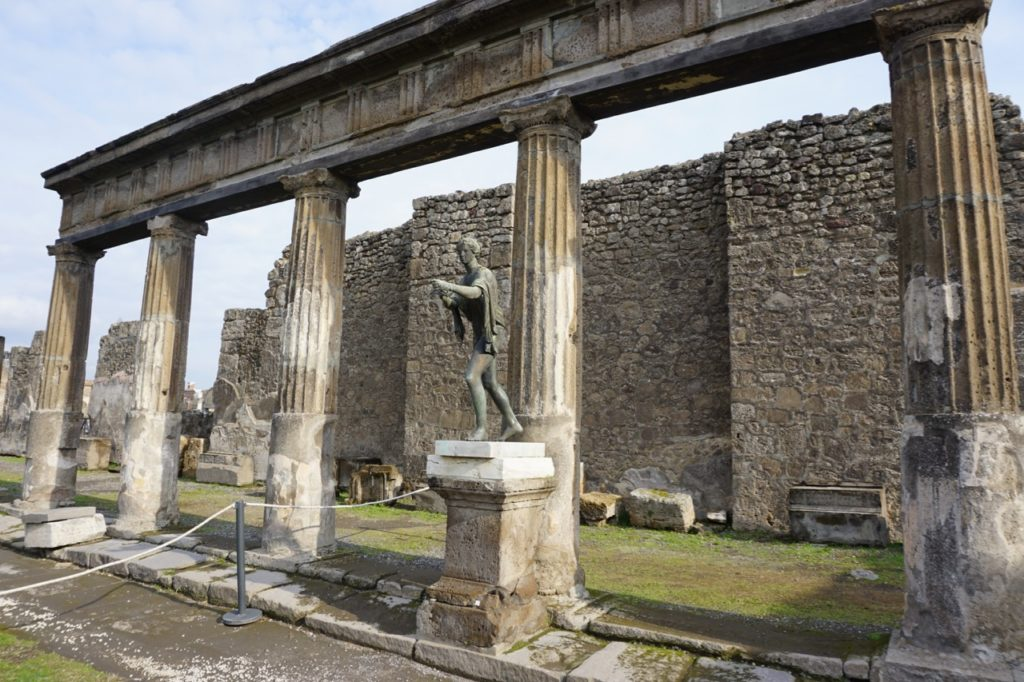Stone statue of a man with stone columns in the background