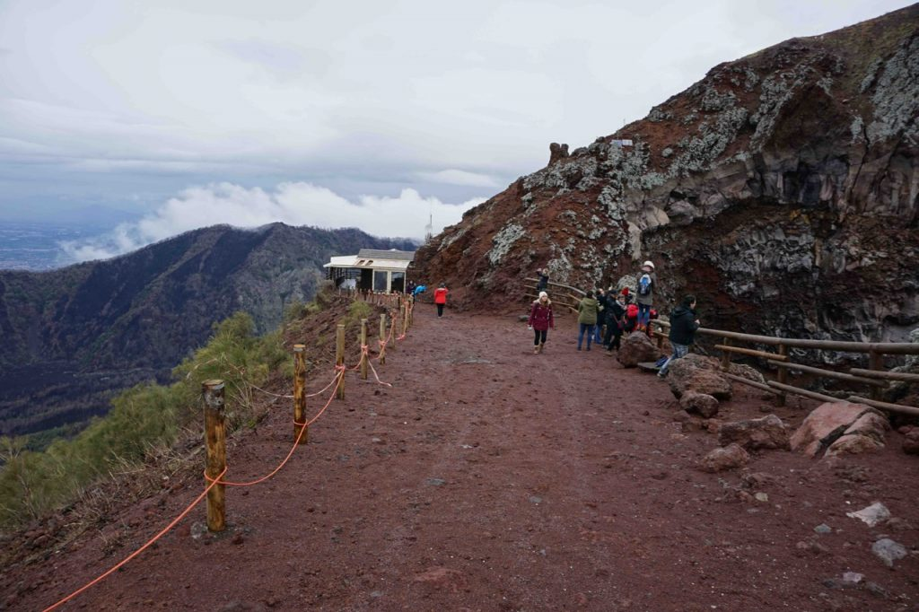 Looking back toward a hit along a brown pathway used for walking up the volcano