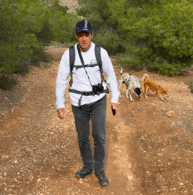 Man with two dogs behind him. One black and white and a smaller brown dog