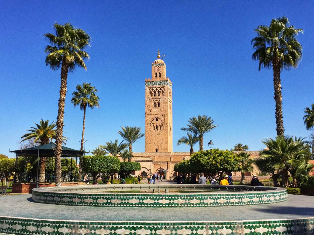 Tall mosque seen over a green mosaic fountain