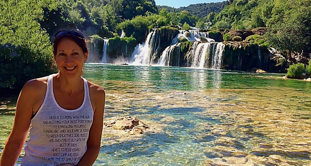 michelle in foreground wearing a white top with Krka Waterfalls in the background - lots of cascading waterfalls on bluey green water