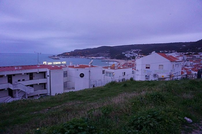Coastal town at dusk seen from a green hill overlooking the beach