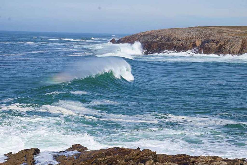 Waves breaking in a rocky inlet with the spray forming a rainbow