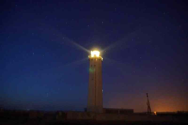 lighthouse beaming its light at night