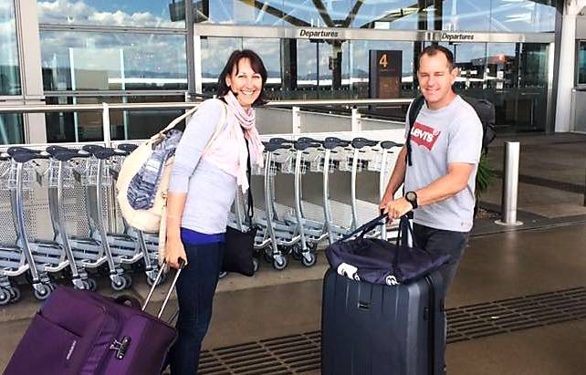 michelle and Lars outside the departures entrance with a large grey suit case and . large purple suitcase