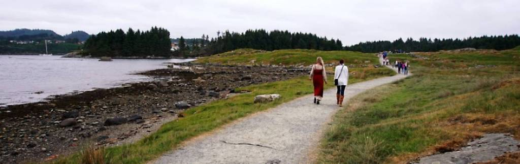 Two women walking across the homeland of the vikings towards the viking farm. Landscape is flat beside path with rough grass .In the distance is the island with pine trees.