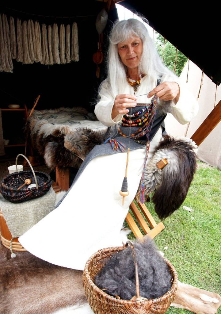 Woman dressed as a viking with a white dress and a blue cloak over top. She has long white hair and holding a woodenspindle and spinning grey wool into yarn