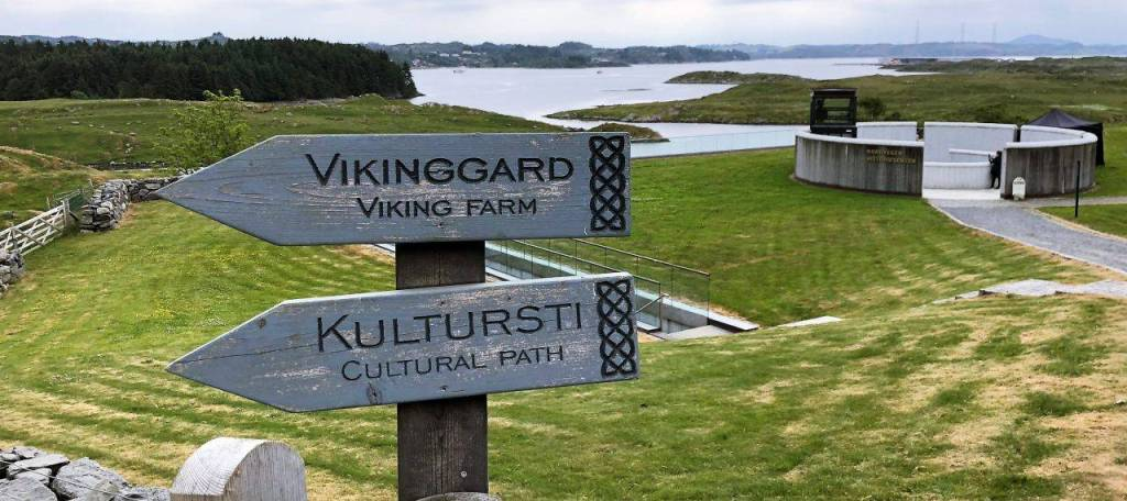 To the left of the picture are two signs that read Viking farm and cultural path. On the right a circular wall which is the entrance to the history centre on the land of the viking kings