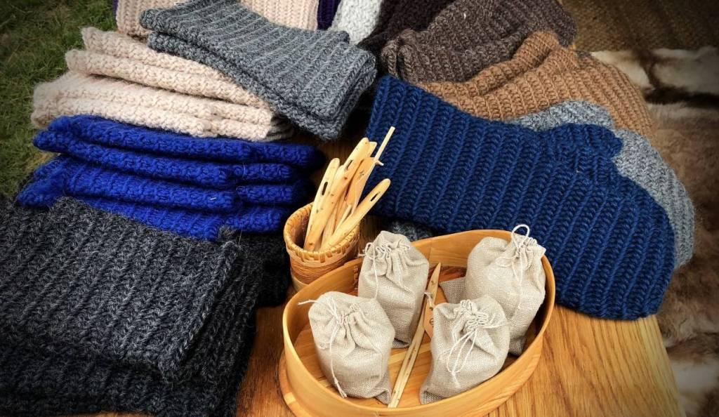 Blue, grey and brown mittens, hats and neck warmers displayed on a table with a pot of wooden large needles.