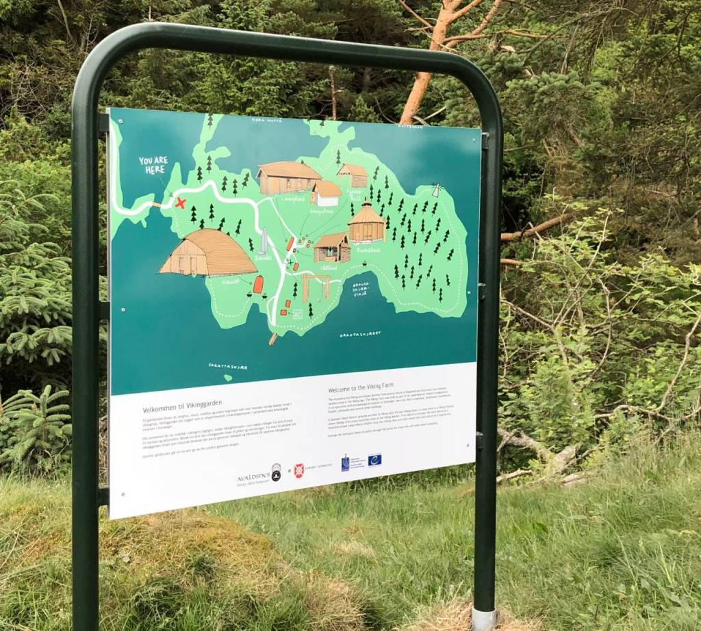 A green sign and map showing the buildings on the viking farm representing a viking settlement