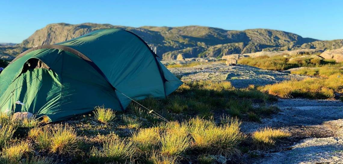 a green small dome shaped tent on rugged landscape with mountains in the background.
