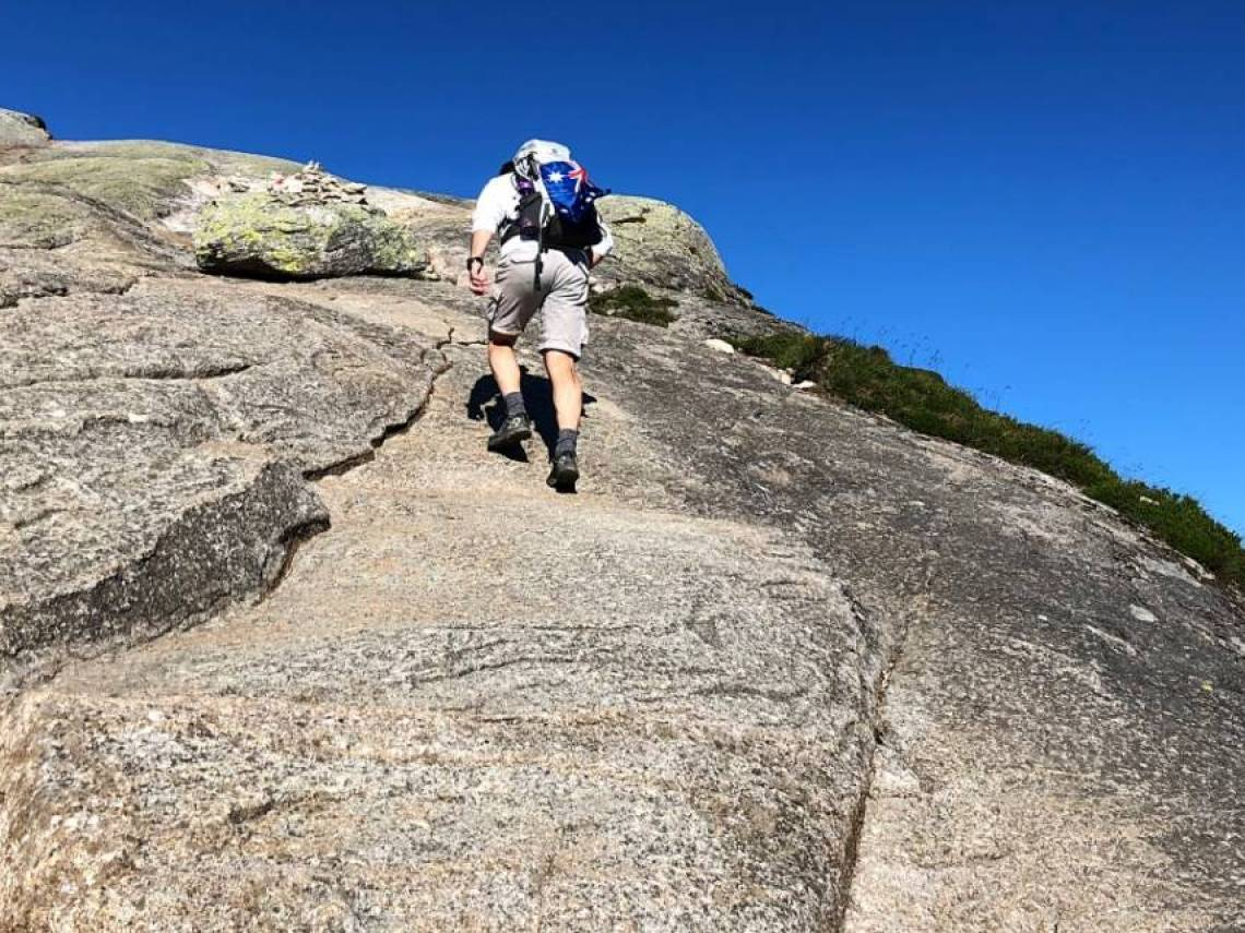Lars ,with back pack on back with australian flag on the bag. He is climbing a granite steep rock.
