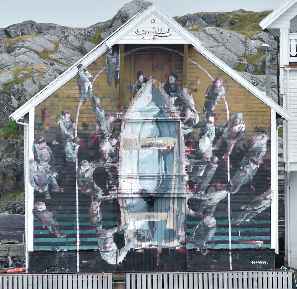 A large mural on the side of a house with a fishing boat in the middle and people stood around it. It is painted from a birdseye view and the colours are mainly pale grey, dark grey brown and blue.