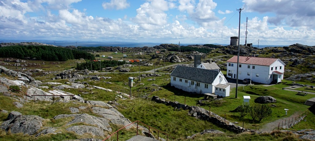 view across Utsira from the top of the lighthouse - can see two buildings and an expansion of green areas with rocks.