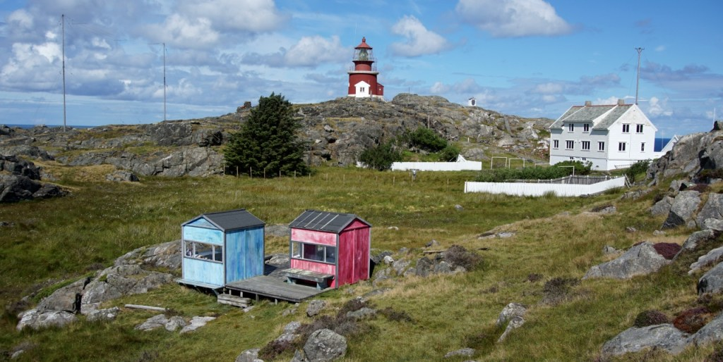 The pink and blue hut with a view of the red lighthouse in the background and the large white house that was the lighthouse keepers quarters.