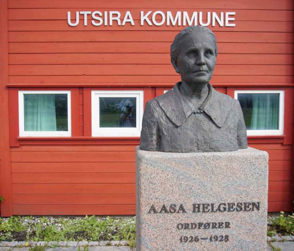 The grey bust of the first mayor of the island, Aasa Helgesen in front of the red wooden building of the Utsira municipality