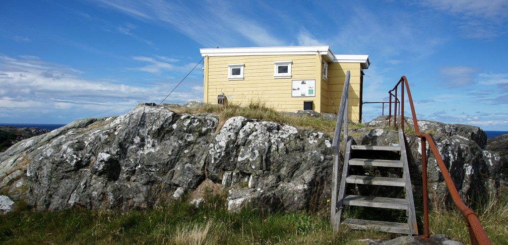 The yellow square hut shown on the top of the hill with 6 wooden steps leading up to it.
