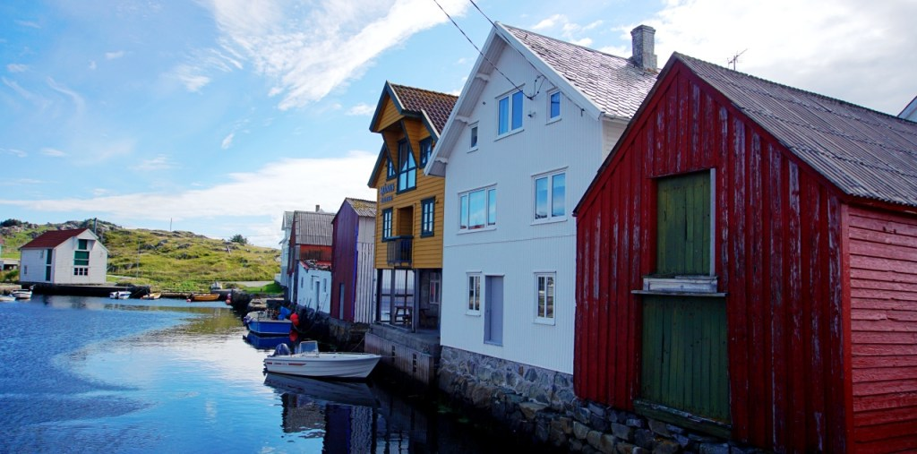 Old North Harbour - Red, white and yellow fishing huts along the side of the water of the calm harbour.