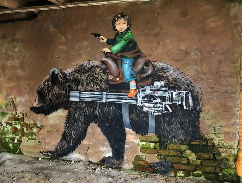 A painting of a big brown bear on the wall with a gun strapped to its side and a young bot riding it with a pistol in his hand