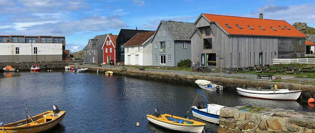 Utsira harbour - od buildings along the side, one red, one white and two weathered wood. There are four small boats in the foreground.