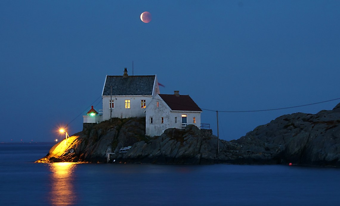 A blood moon, looking pinkish as it is in the shadow of the Earth. over head two white houses, beside a small lighthouse. The houses are on rocks surrounded by the ocean
