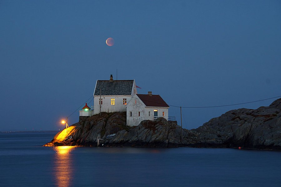 Blood moon over a lighthouse near the water