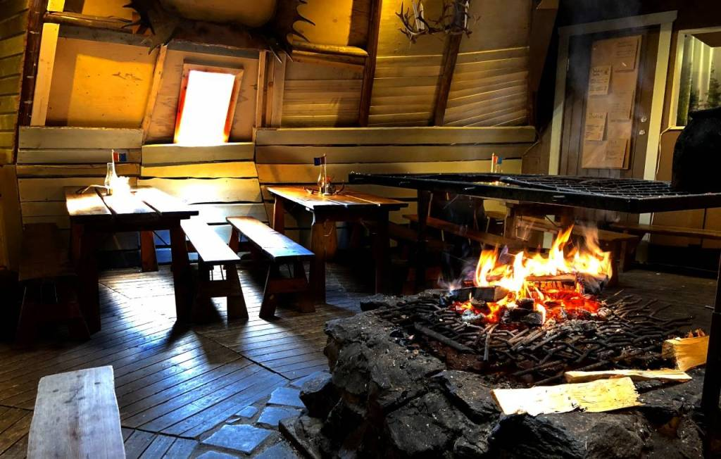a photo of inside the cafe - with an open fire for cooking in the middle of the room. Tables and benches can be seen in the background.