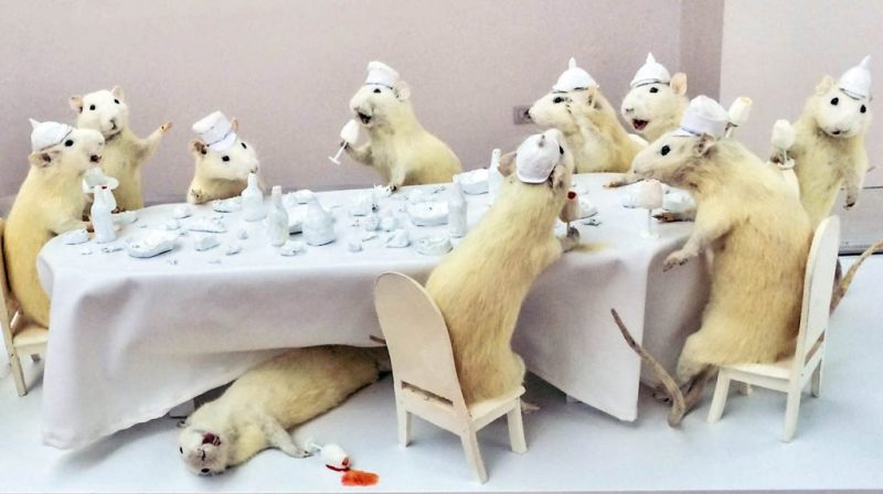 10 stuffed white dwarf hamsters in poses around a white table that is sized relative to them.