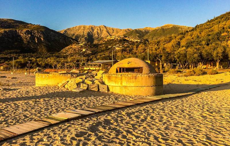 a golden tinge of sunset is on the mushroom shaped bunker on the beach. There are large mountains in the distance.