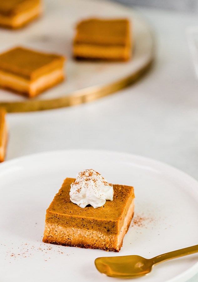 Top view of keto pumpkin pie bar on a white plate with a fork