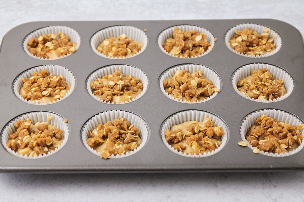 Apple muffins with oat topping in a muffin tin