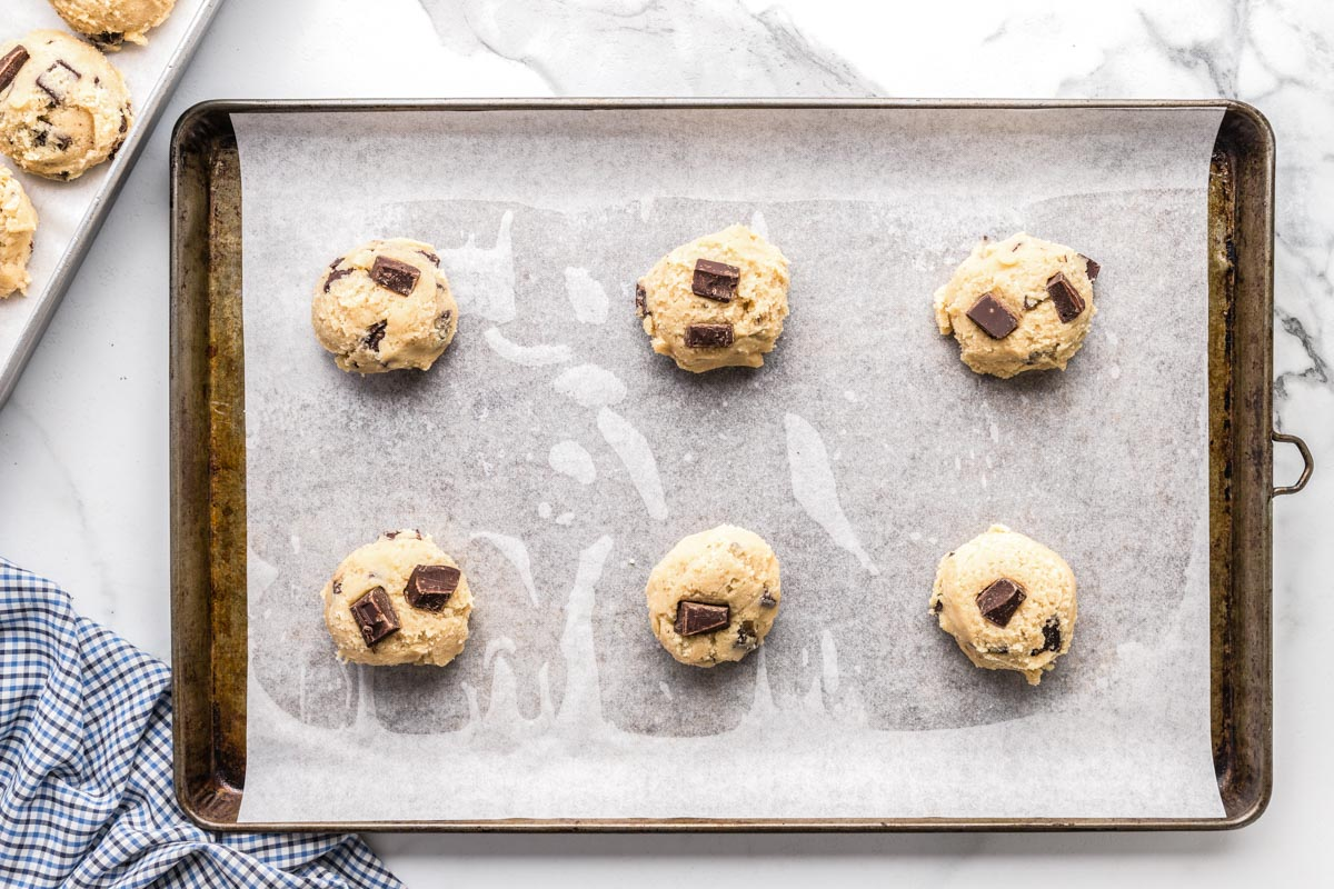 Scoops of chocolate chunk cookie dough on a baking sheet