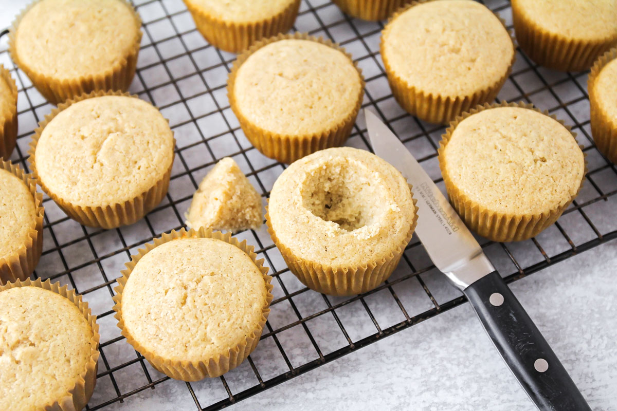 cutting holes into apple pie cupcakes for filling