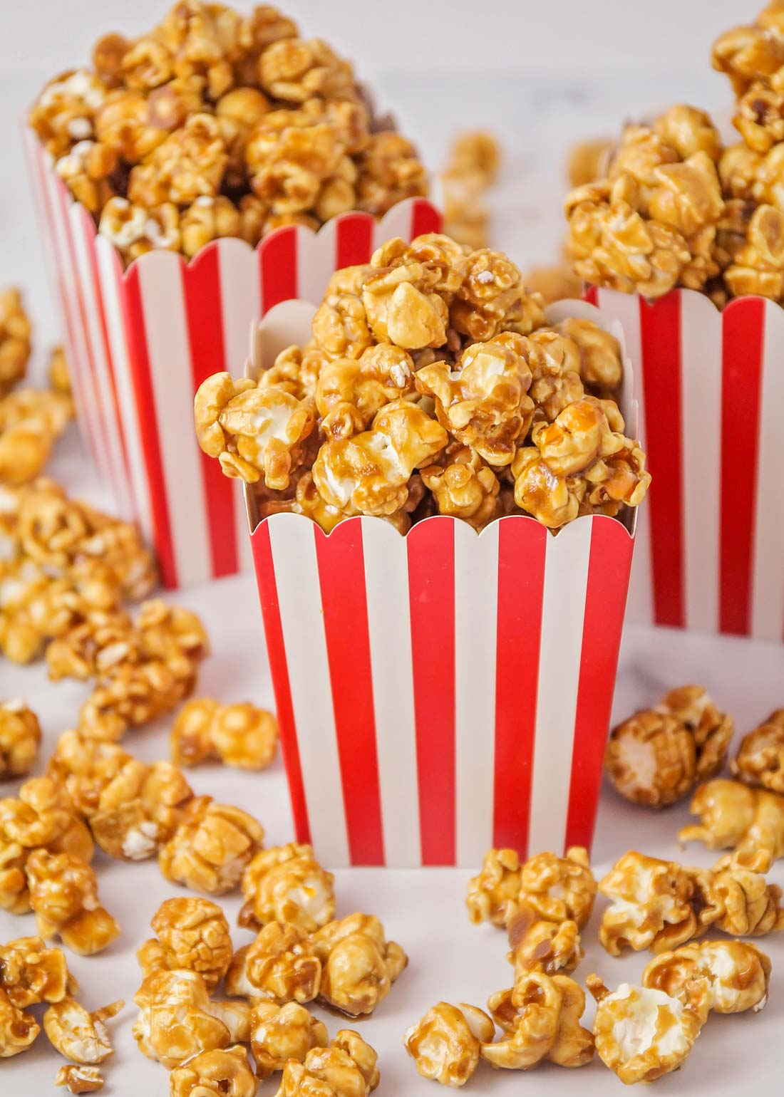 Homemade caramel corn in striped popcorn containers