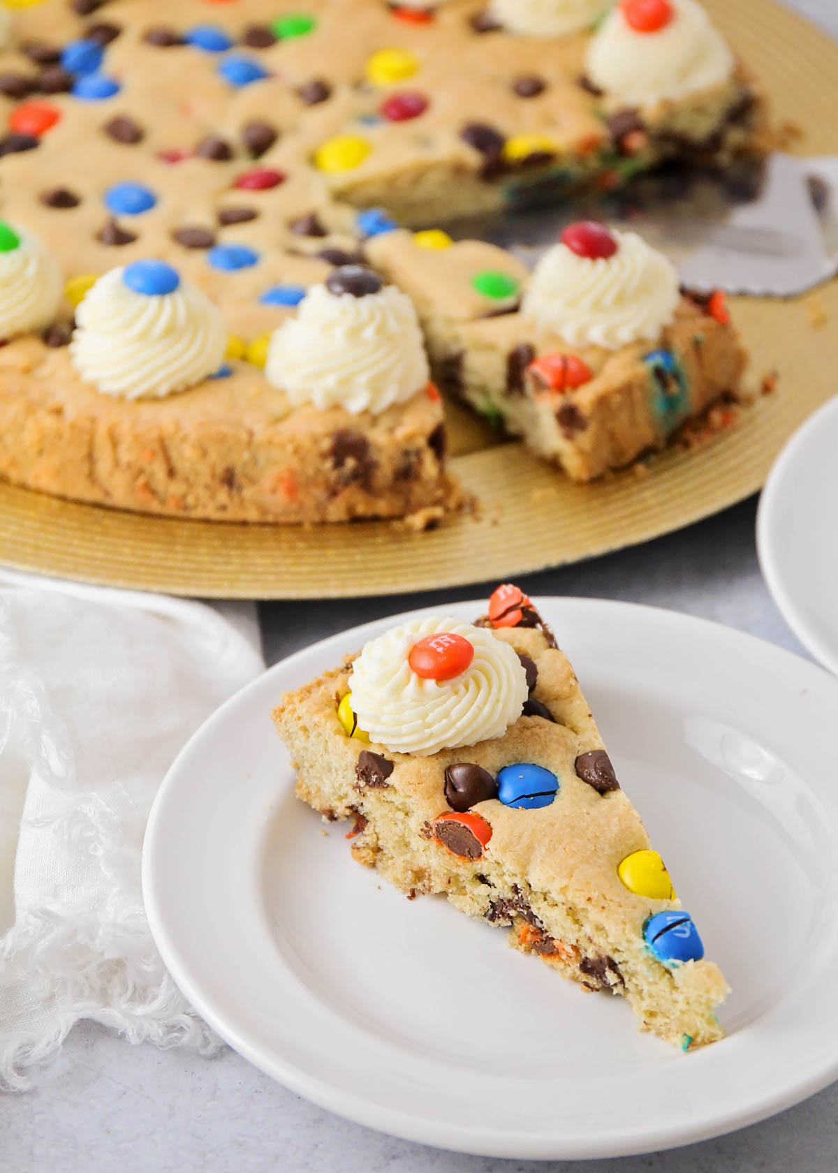 A slice of homemade cookie cake on a white plate