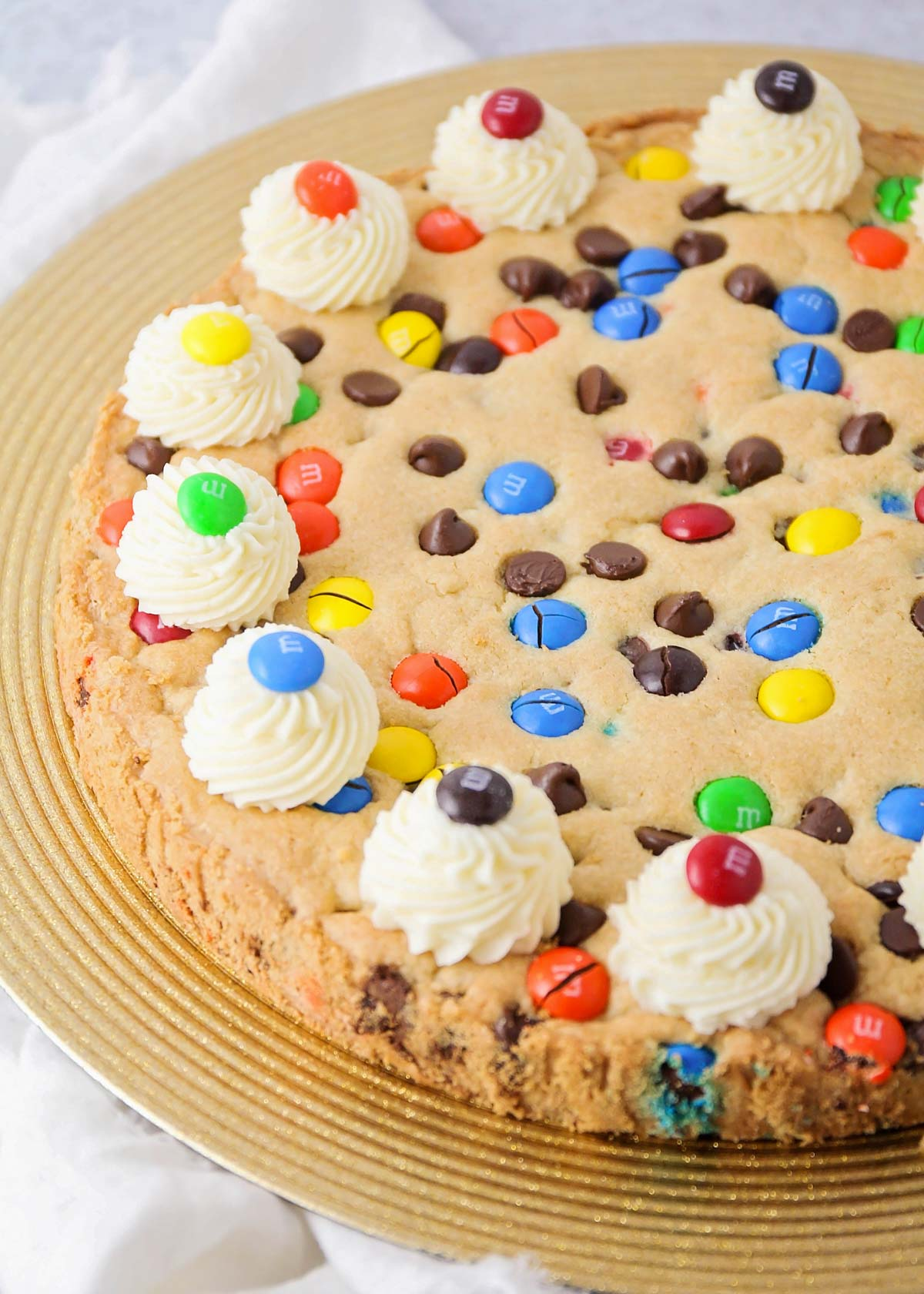 Close up of a homemade cookie cake topped with frosting and M&M's