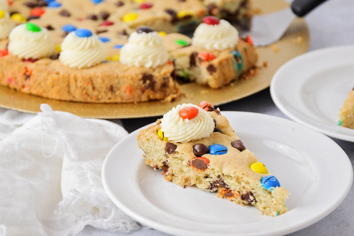 A slice of cookie cake on a white plate