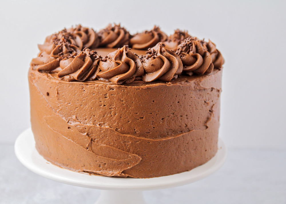 Chocolate cake sitting on top of a white cake stand