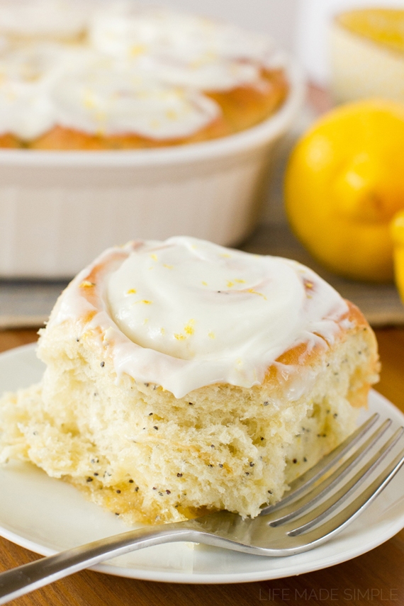 Lemon poppy seed roll on a white plate with a fork