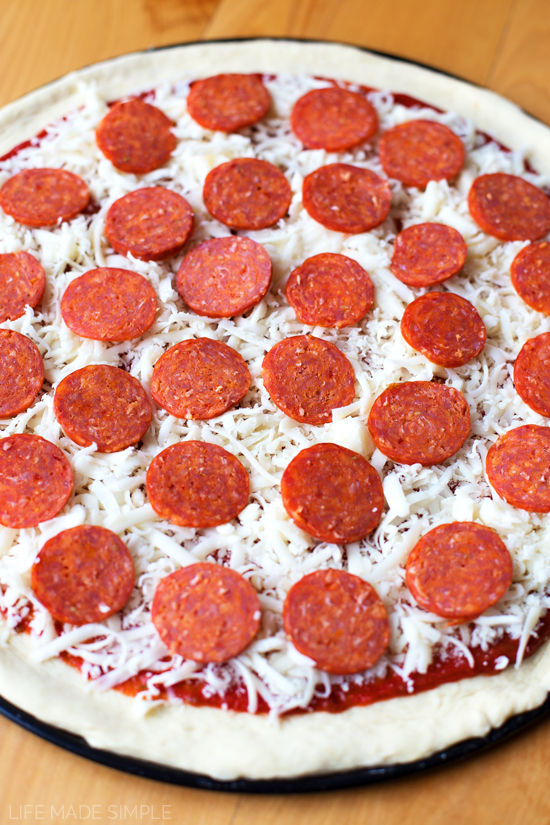An unbaked pepperoni pizza