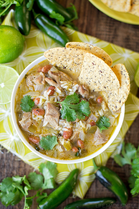 A bowl of pork chile verde soup with tortilla chips