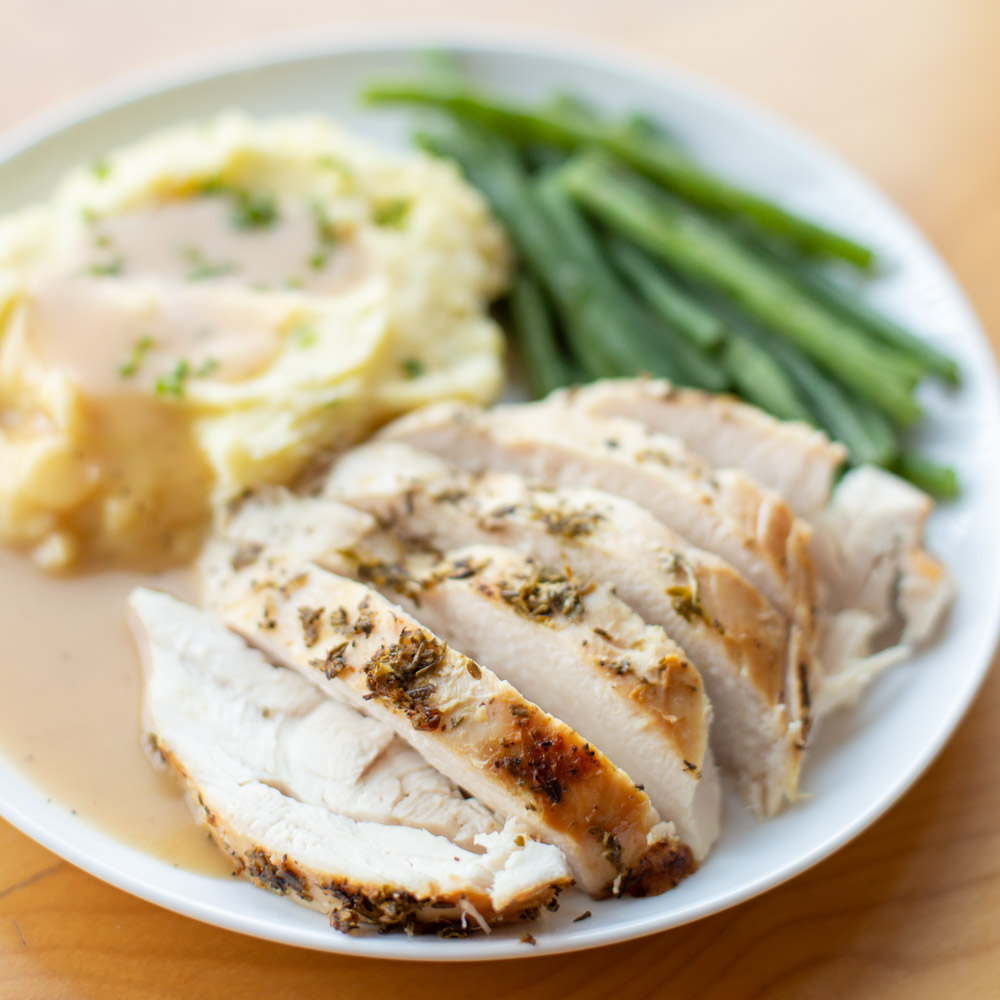 Oven roasted turkey recipe on plate with green beans and mashed potatoes