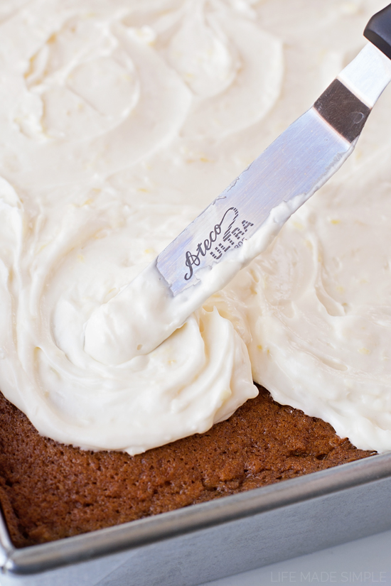 Spreading Pineapple Cream Cheese Frosting on carrot sheet cake
