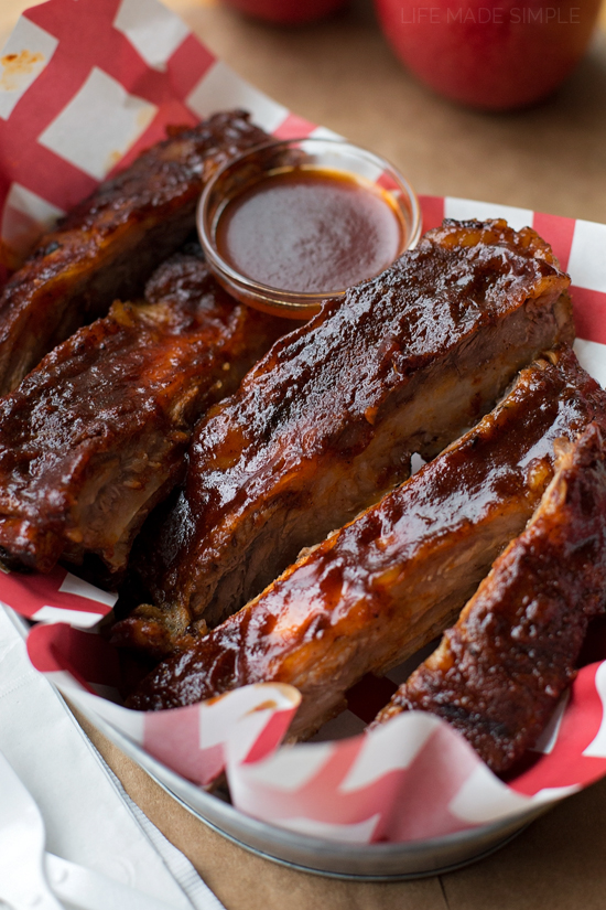 Baked BBQ Ribs served in a basket with bbq sauce on the side
