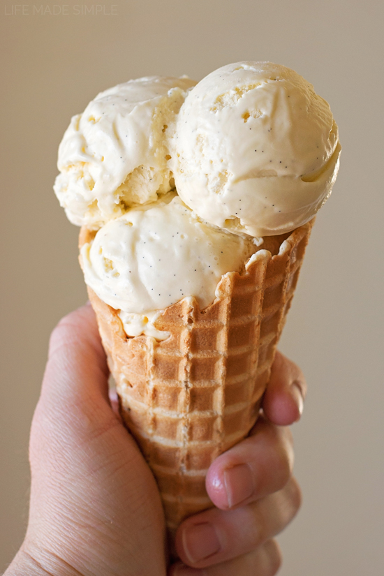 Three scoops of vanilla bean ice cream in a waffle cone