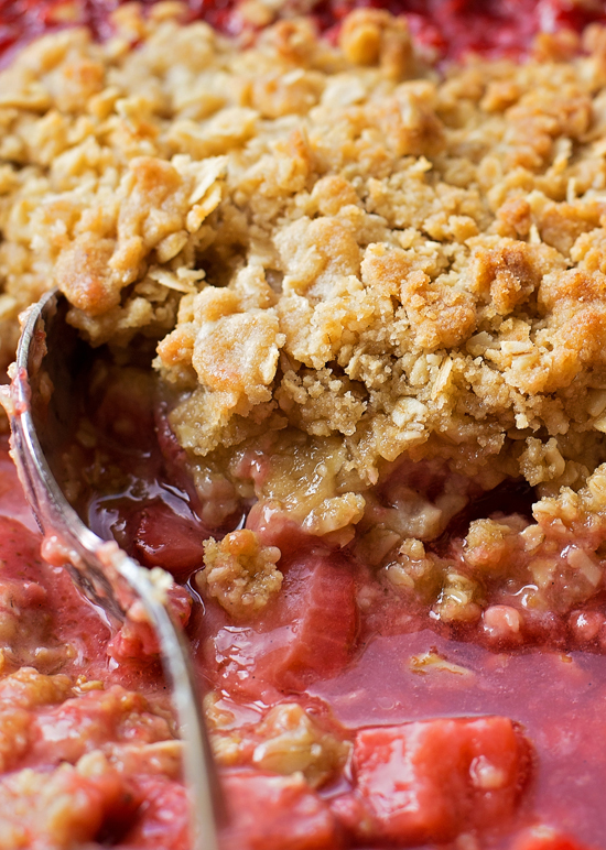 Close up of Strawberry Rhubarb Crisp with a spoon