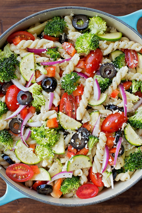 Summer pasta salad with broccoli, tomatoes, zucchini, peppers, olives, and onions