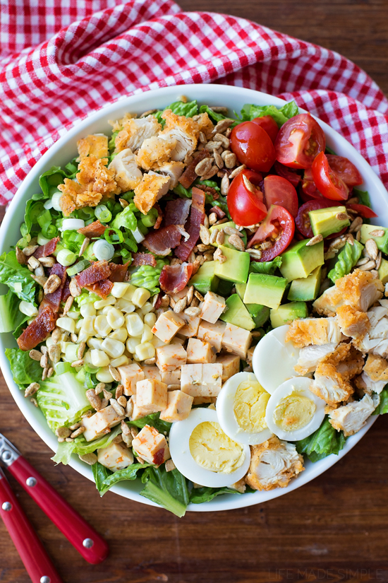 Cobb salad with eggs, chicken, bacon, tomato, corn, and avocado in a bowl