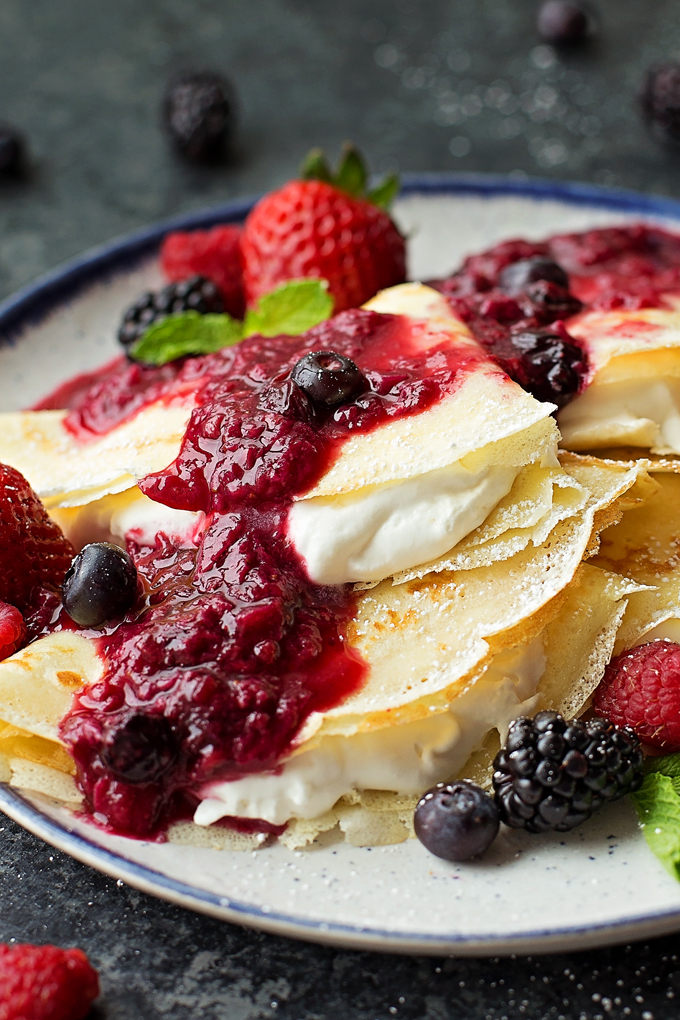 Homemade crepes filled with cream and topped with berries