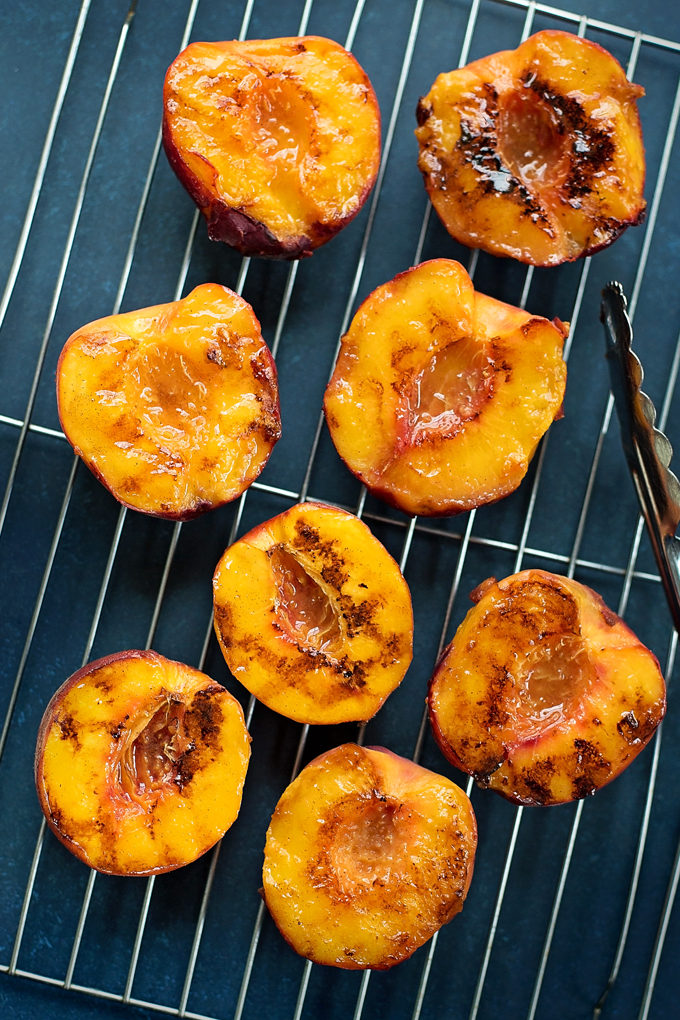Grilled peaches on a wire rack with grilling tongs
